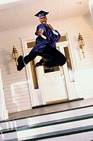 Teenage boy in a graduation outfit leaping on the porch