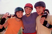 Portrait of a group of three teenagers wearing helmets smiling