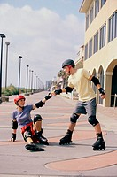 Young man helping up a young woman on in-line skates