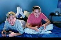 Teenage boy and girl sitting on the bed and playing a video game