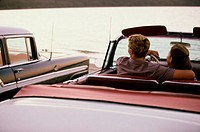 Rear view of a young couple sitting in a convertible car