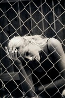 Teenage girl sitting behind a chain-link fence