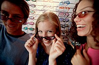 Close-up of a young man and two young women wearing sunglasses