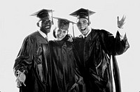 Portrait of two young men and a young woman in graduation outfits