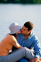 Young couple sitting outdoors kissing
