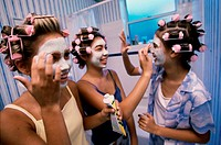 Three teenager girls applying facial masks
