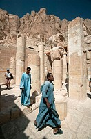 Temple caretakers walk through the broken columns at the Mortuary Temple of Hatshepsut (Deir el-Bahri)