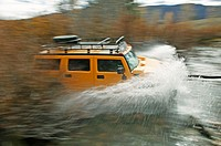 A Hummer splashing through a creek. Boulder City, Idaho. USA