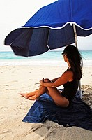 Woman sitting under an umbrella on Saline Beach, St. Barts