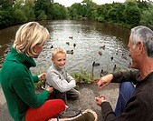 Happy Family feeding Ducks by a Pond
