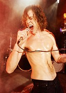 Topless Male Rock Singer Stands on a Spotlit Stage Screaming Into a Microphone