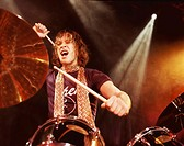 Drummer in a Rock Band Performs on a Spotlit Stage, Hitting the Cymbal of His Drum Kit and Shouting