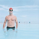 Senior Man in a Swimming Cap and Goggles Stands in a Swimming Pool