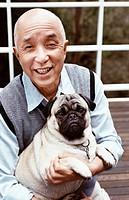 Portrait of a Senior Man Holding His Pet Pug Dog