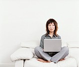 Woman Sitting Cross-legged on a White Sofa, Looking Sideways and Using a Laptop Computer