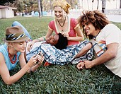 Four Young Men and Women Hang Out in the Park, Lying on the Grass