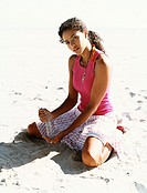 Young Woman Kneels on the Sand, Pouring it Through Her Fingers