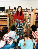 Portrait of a Teacher Reading a Story Book to a Small Group of Children in a Library