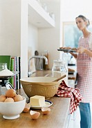 Eggs, Kitchen Scales, Butter and a Bowl With Spoon on KitchenCounter, Woman Holding a Baking Tray on Background