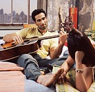Twentysomething Couple on a Bed in an Apartment, Man Playing an Acoustic Guitar