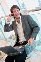 24 year old man sitting in chair talking on mobile phone, smiling, working on laptop