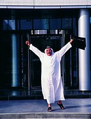 Jubilating Arab businessman in front of office building
