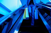 Woman with shopping bags using escalator (thumbnail)