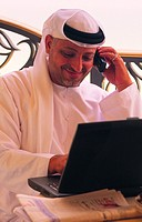 Smiling Arab businessman with laptop and mobile phone