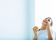 Woman holding apple and laughing, on phone