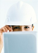Woman wearing hard hat, looking over computer screen