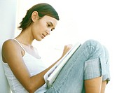 Young woman sitting with knees up, writing, side view