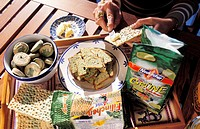 Algae food products. Tray of various biscuit and bread products that have seaweed and other algae in them. Butter is being spread on a biscuit to be e...