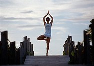 Rear View of a Young Woman Stands on a Boardwalk in a Yoga Pose