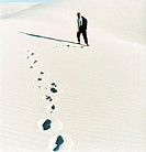 Rear View of a Businessman Walking in the Desert, His Footprints in the Sand