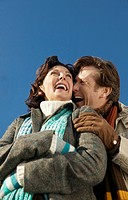 Low Angle View of a Mature Couple in Winter Clothing Embracing and Laughing