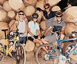 Portrait of Four People Sitting on Logs With Their Mountain Bikes