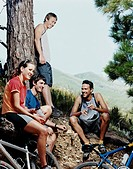 Four People Resting by a Tree Trunk With Their Mountain Bikes