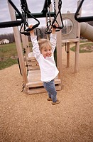 Little girl hangs from playground climber. USA