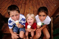Three kids eat vanilla ice cream cones. USA