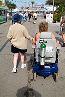 Handicapped person with oxygen tank in motorized wheelchair.