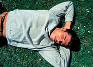 man lying down on field, sleeping