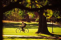 Girl with backpack rides bike across college campus. Pennsylvania, USA