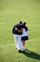 College field hockey player hugs her dad following field hockey match. Pennsylvania, USA