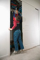 Boy trying to reach shelf in wardrobe