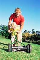 Father and son pushing lawn mower
