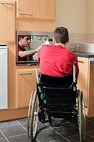 Disabled man opening oven