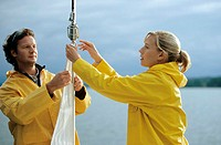 Couple adjusting sail on boat