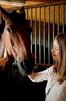 Young woman stroking horse's face
