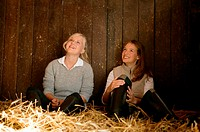 Two young women in a stable
