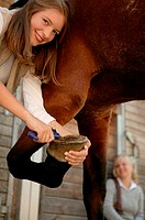 Young woman cleaning horse's hoof